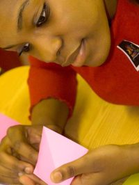 A student concentrates on the first folds of an origami crane, December, 2010
