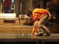 NYC i-School student laying paper cranes on the stage