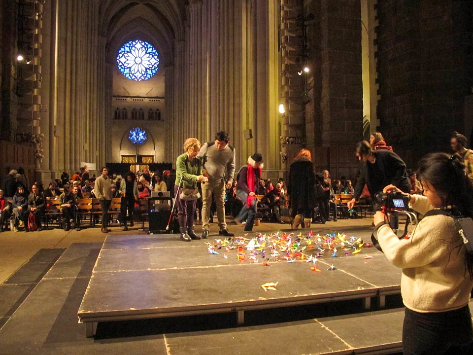 Audience members laying paper cranes on the stage