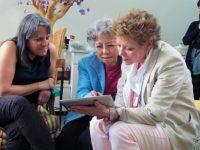 Shigeko Sasamori shows photos of her grandchildren to Debbie Brindis and Sandy Parker