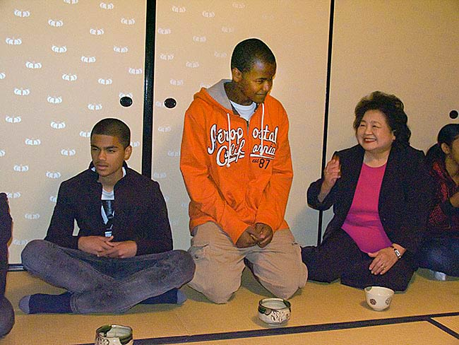 Setsuko Thurlow congratulates a student upon drinking his entire cup. The tea tastes strange to young people not accustomed to its bitterness.