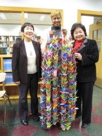 Jane Addams Principal Sharron Smalls gives 1,000 paper cranes to Toshiko Tanaka and Setsuko Thurlow