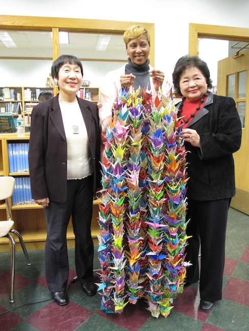 Jane Addams Principal Sharron Smalls gives 1,000 paper cranes to Toshiko Tanaka and Setsuko Thurlow