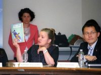 Kathleen Sullivan shows her book Action for Disarmament: Ten Things You Can Do! to Emilie McGlone and Akira Kawasaki