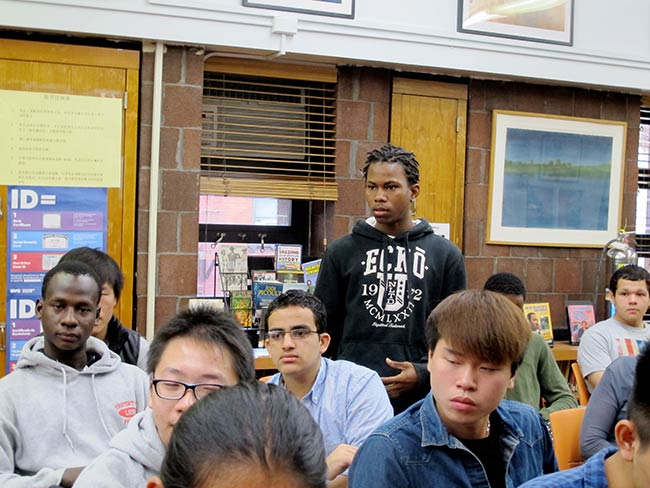 A student asks a question at East Side Preparatory