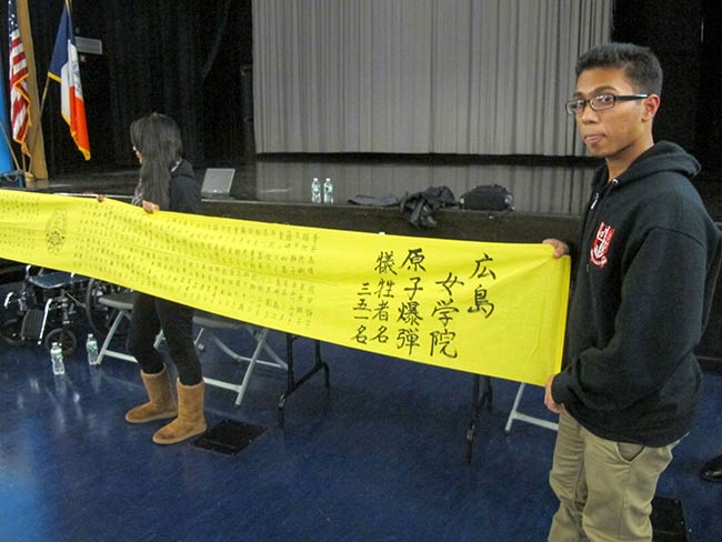 Students at Aspirations High with a banner from Jogakuin High School commemorating the girls who lost their lives August 6, 1945