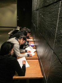 Students write responses in the Japan Society hallway