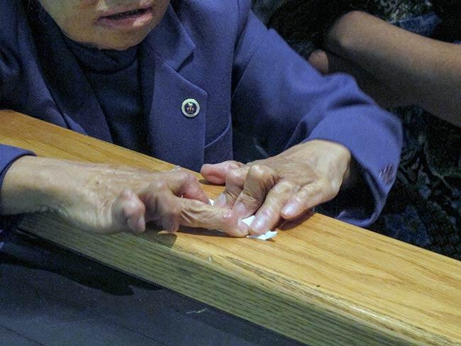 Shigeko Sasamori making an origami crane, Mott Haven
