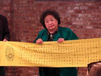 Setsuko Thurlow & banner with names of her classmates who perished